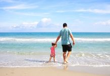 Father and daughter going out to enjoy summer vacation near beach