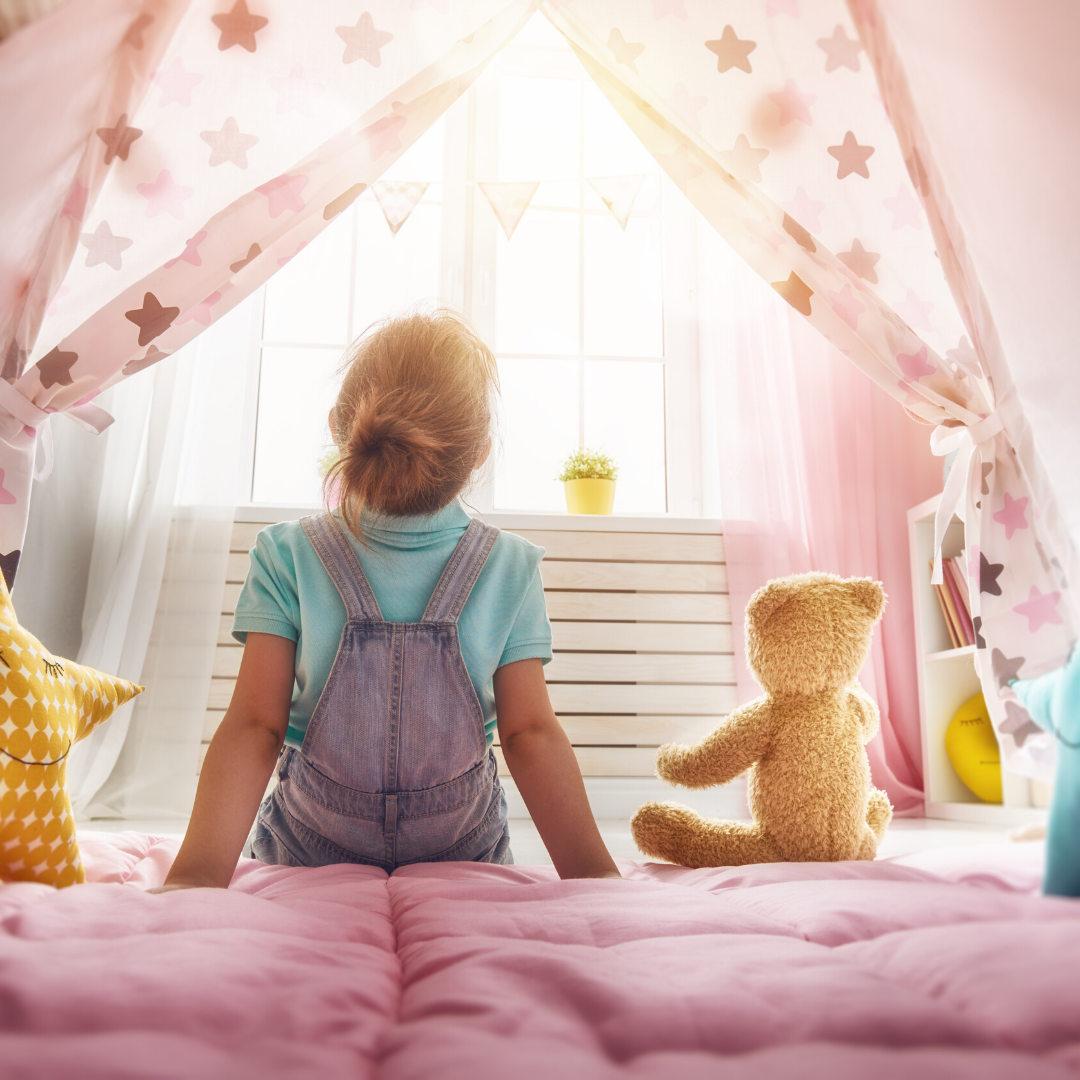 child sitting on bed with stuffed animal